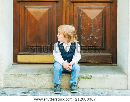 Outdoor portrait of a cute toddler boy, sitting on steps in a city, wearing beautiful celebration clothes - stock photo