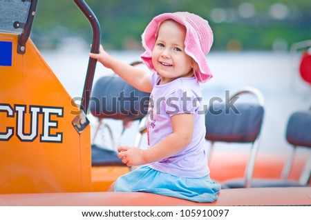 Outdoor portrait of a cute toddler girl sitting in a surf rescue boat - stock photo