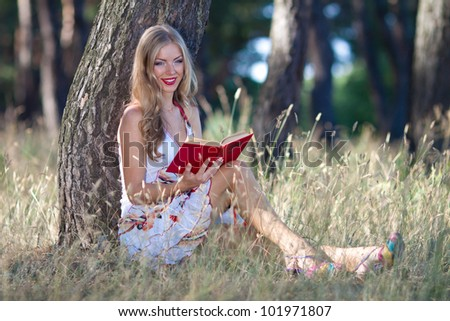 Outdoor portrait of a cute woman sitting under a tree and reading a book - stock photo