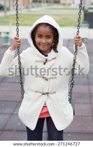 Outdoor portrait of a cute young black girl playing with a swing - African people - stock photo