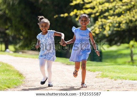 Outdoor  portrait of a cute young black sisters running - African people - stock photo