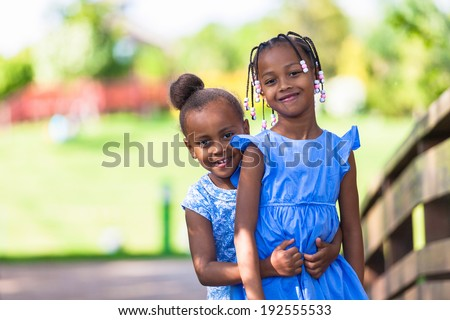 Outdoor  portrait of a cute young black sisters smiling - African people - African people - stock photo