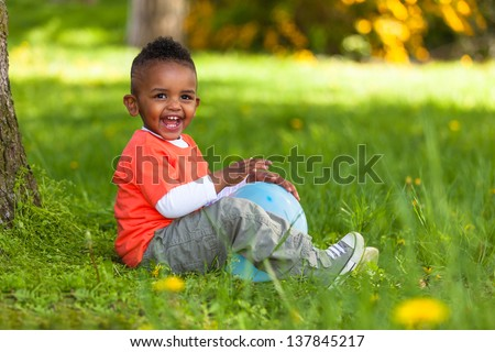 Outdoor portrait of a cute young  little black boy playing with a balloon - African people - stock photo