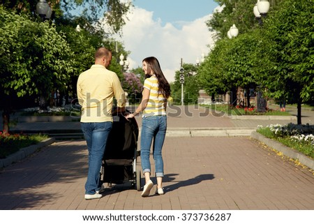 outdoor portrait of a family with baby in stroller. young parents with a baby in pram for a walk in the summer park. Mom, dad and child - stock photo