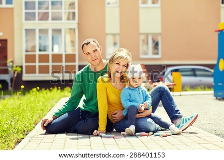 outdoor portrait of a family. young parents with a baby for a walk in the summer park. Mom, dad and child - stock photo