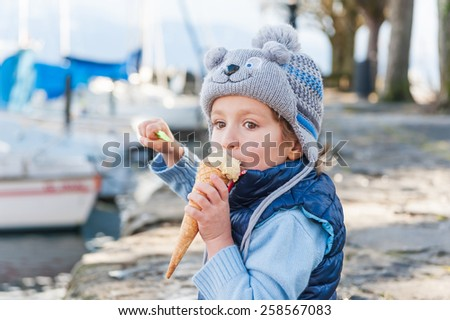 Outdoor portrait of a funny little boy eating ice cream, wearing winter hat - stock photo