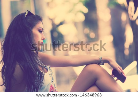 outdoor portrait of a girl sitting holding cell phone in hand side view retro colors - stock photo