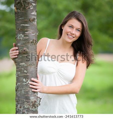 Outdoor portrait of a happy young woman in summer - stock photo
