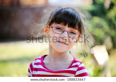 Outdoor portrait of a little child girl in spectacles - stock photo
