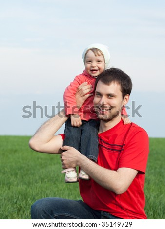 Outdoor portrait of a little girl sitting on father's shoulder - stock photo