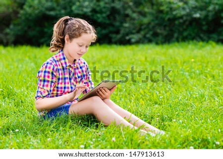 Outdoor portrait of a pretty teenager girl in casual clothes sitting on the grass with digital tablet on her knees, reading and surfing - stock photo