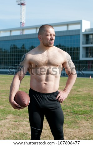 Outdoor portrait of a serious player holding an american football - stock photo