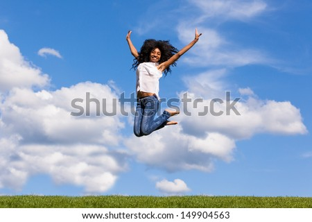 Outdoor portrait of a smiling teenage black girl jumping over a blue sky - African people - stock photo