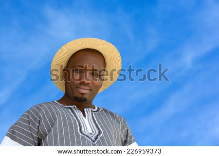Outdoor portrait of a South African black man with friendly smiling facial expression on a blue sky background. - stock photo
