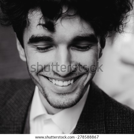 outdoor portrait of a very beautiful sexy young man, dark hair, with a stunning smile, smiling and posing in an old courtyard   a classic suit - stock photo