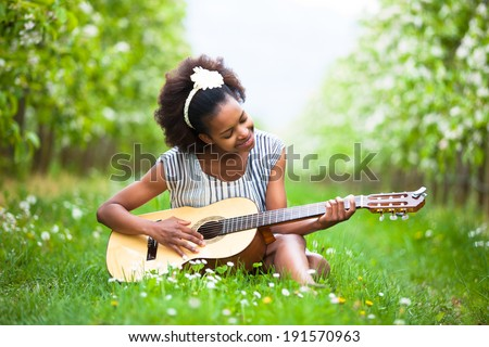 Outdoor portrait of a young beautiful african american woman playing guitar - Black people - stock photo