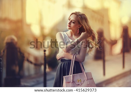 Outdoor portrait of a young beautiful fashionable lady walking on street. Model wearing stylish clothes. Girl looking aside. Female fashion. City lifestyle. Toned style instagram filters   - stock photo