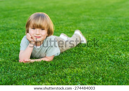 Outdoor portrait of adorable little blond boy laying on a bright fresh green lawn - stock photo