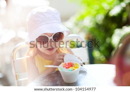 Outdoor portrait of adorable little girl eating ice cream - stock photo