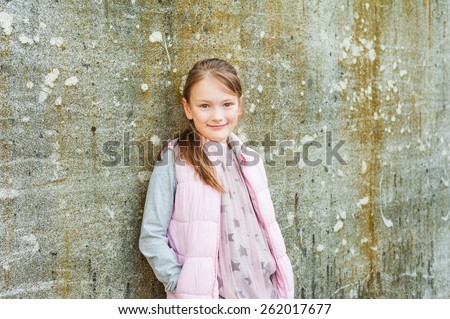 Outdoor portrait of adorable little girl of 7 years old, wearing light pink waistcoat and dress, standing against stone wall - stock photo