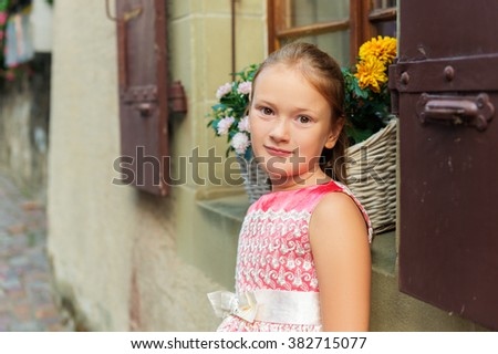 Outdoor portrait of adorable little girl of 7-8 years old, wearing party dress - stock photo