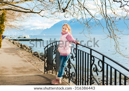 Outdoor portrait of adorable little girl wearing pink jacket and warm boots. - stock photo