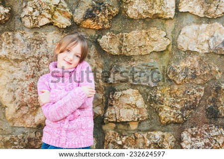 Outdoor portrait of adorable little girl wearing pink pullover - stock photo