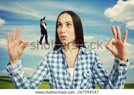 outdoor portrait of amazed woman and small man on the rope - stock photo