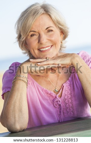 Outdoor portrait of an attractive elegant classy senior woman happy & smiling - stock photo