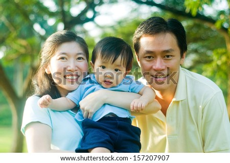Outdoor portrait of asian family - stock photo