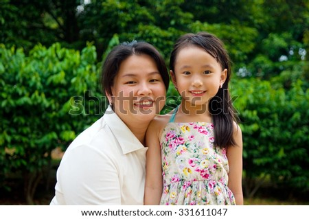 Outdoor portrait of asian mother and her lovely daughter - stock photo