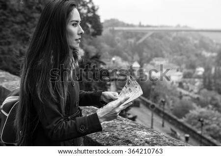 Outdoor portrait of attractive young woman with long beautiful hairs and city map on her hands. - stock photo