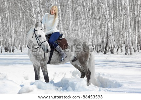 outdoor portrait of beautiful blonde girl sitting on pale horse in sunny winter forest - stock photo