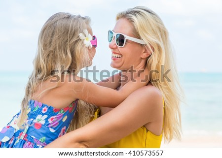Outdoor portrait of beautiful blonde mother and her cute daughter. Small girl and her mammy look to each other and smile. Little lady and mom wearing sunglasses. Summer sunny day. Happy Mothers day. - stock photo