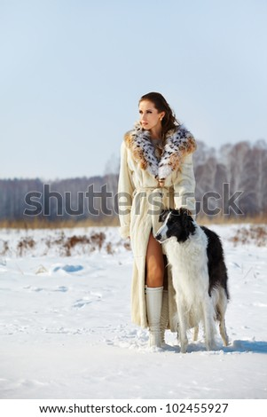 outdoor portrait of beautiful brunette woman with borzoi in snowy filed with winter forest on background - stock photo
