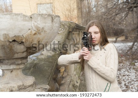 Outdoor Portrait of beautiful caucasian cute woman with brown long hair holding vintage 8mm camera in hands Outdoor in winter snowy park and based on old retro concrete fence - stock photo
