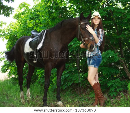 Outdoor portrait of beautiful cowgirl with horse in the green forest - stock photo