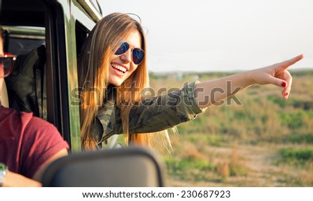 Outdoor portrait of beautiful girl on car roadtrip pointing forward.  - stock photo