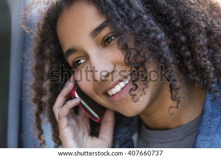 Outdoor portrait of beautiful happy mixed race African American girl teenager female young woman smiling with perfect teeth talking on cell phone - stock photo