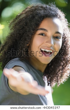 Outdoor portrait of beautiful happy mixed race African American girl teenager female young woman smiling with perfect teeth holding hand to camera - stock photo