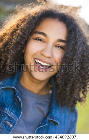 Outdoor portrait of beautiful happy mixed race African American girl teenager female young woman smiling laughing with perfect teeth - stock photo