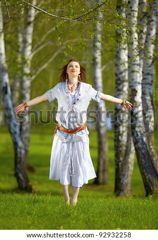 outdoor portrait of beautiful hippie girl jumping on green grass in birch forest - stock photo