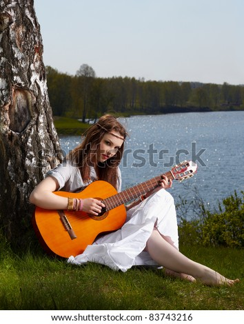 outdoor portrait of beautiful hippie girl sitting on green grass near birch with guitar. lake and forest on background - stock photo