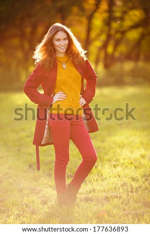 Outdoor portrait of beautiful redhead woman in red cloak - stock photo