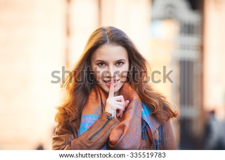 Outdoor portrait of beautiful redhead young woman covering her mouth with finger - stock photo