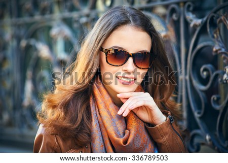 Outdoor portrait of beautiful redhead young woman in sunglasses - stock photo