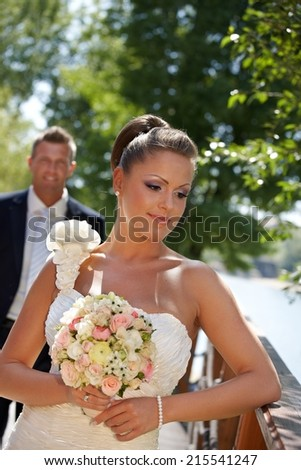 Outdoor portrait of beautiful young bride in wedding gown. - stock photo