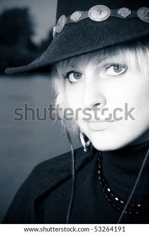outdoor portrait of beautiful young woman cowgirl in hat, B&W - stock photo