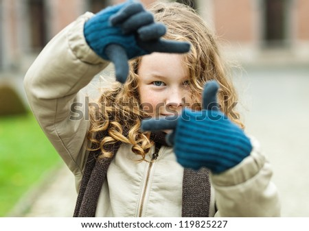 Outdoor portrait of blond teenager girl framing her view with the fingers - stock photo