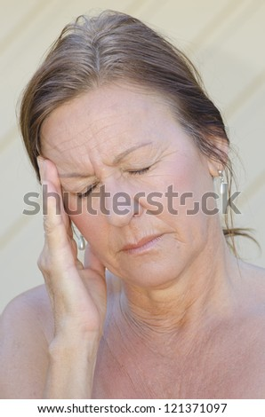 Outdoor portrait of concerned woman in pain, depression, in menopause with hand holding head, isolated with blurred background. - stock photo
